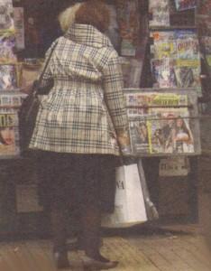 Натоварената с покупки юристка се запаси и с вестници и списания от улична будка. Четенето е едно от малкото й развлечения.