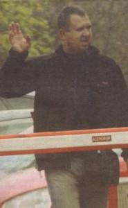 Дружелюбният реквизитор поздравява охраната на паркинга. Той се опитва и да се усмихне, но на лицето му се изписва само жалка гримаса.