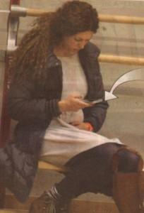 Бременната Гергана гали наедрялото си коремче, под което расте детето й, докато комуникира по смартфона си.